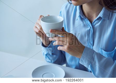 The girl drinks coffee, the girl drinks tea, the girl holds a mug sitting at a table.