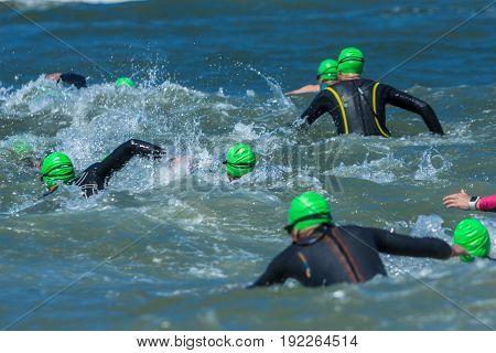Kijkduin The Hague the Netherlands - 17 June 2017: Kijkduin cross triathlon athletes running into the sea for swim leg