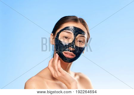 Black cosmetic face mask, coal face mask, girl on a blue background.