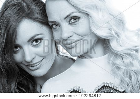 Generation relationship concept. Portrait adult daughter with mother. Two beautiful elegant women long curly hair blonde mom and brown haired girl