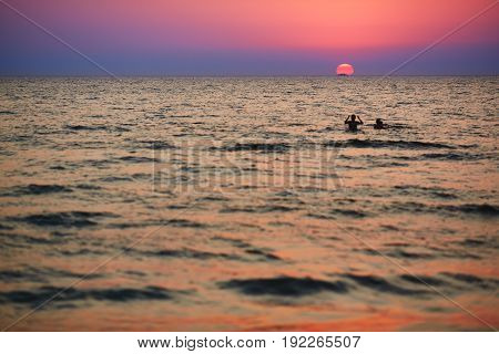 Silhouettes of children playing in the waves at sunset and silhouette of the ship in the background of the sun