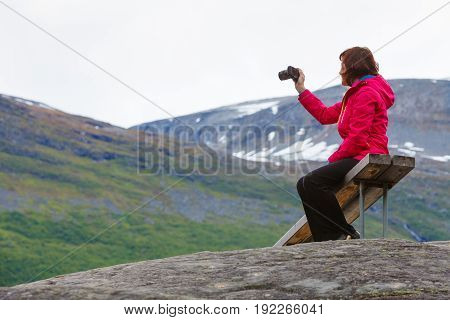 Tourism adventure and travel. Female tourist hiker sitting on bench in stone mountains taking photo with camera looking at scenic view Norway Scandinavia.