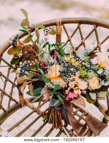 Gorgeous wedding bouquet consisting of different flowers lying on an old brown chair. Bunch of flowers. Close-up