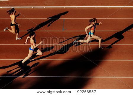 Chelyabinsk Russia - June 4 2017: three women runners shadows running sprint race during UrFO Championship in athletics