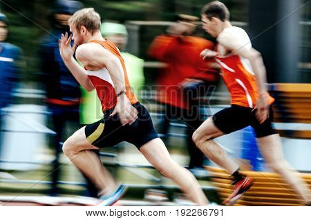 Chelyabinsk Russia - June 4 2017: blurred motion two runners men run in stadium during UrFO Championship in athletics
