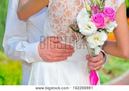 The Wedding Ring: Groom Hand Embraces The Waist Of The Bride. Wedding Bouqet. Close Up