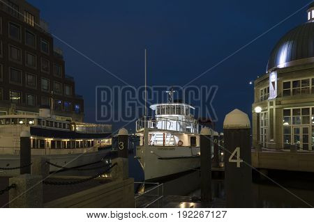 Boston Massachusetts USA - January 19 2017: Cruise boat Northern Lights glowing in pre-dawn winter darkness at Rowes Wharf on Boston waterfront