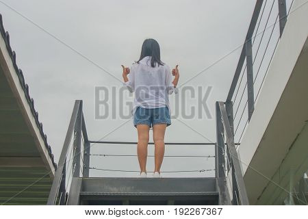 Business Success Concept : Asian woman standing on top of stair with raise up her hands and giving a thumbs up gesture.