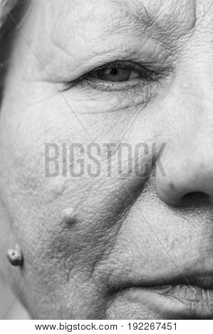 Details of senior woman half face. Elderly pensioner female cheek close up.