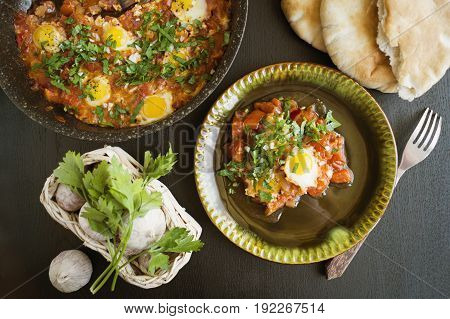 Shakshouka with pita bread on the pan. In the middle East a traditional dish. Scrambled eggs with tomatoes peppers vegetables and herbs. Shakshuka on the table. The view from the top.