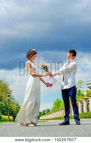 Young And Handsome Newlyweds On A Walk In The Park: Give Flowers