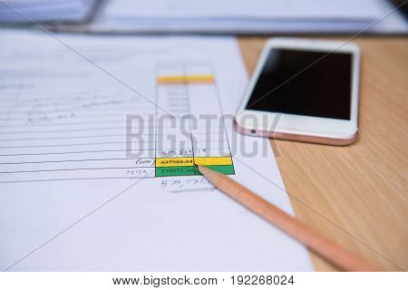 Closeup  pencil with  finance business sheet and phone . Business concept. On wooden table.