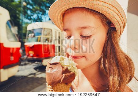 Summer day in the city. Cute little girl with hat eating big ice cream