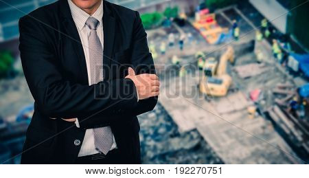 Male model in a suit posing on construction site from a high angle.