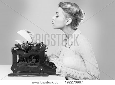 Young adult white female using antique vintage typewriter. Black and white.