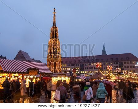 Nurenberg, Germany - December 10, 2014: Christmas market in the evening. A multitude of wooden houses decorated selling Christmas products