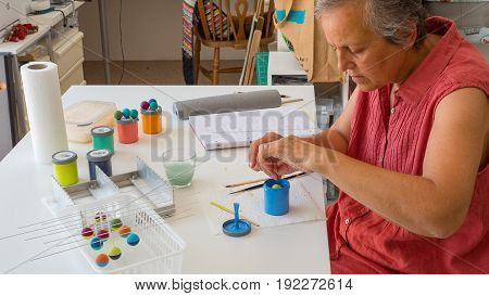 woman painting polymer clay beads. Handmade workshop composition of clay, beads, tools and paint in studio