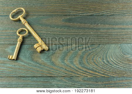 A rustic wooden board with two old keys as a background
