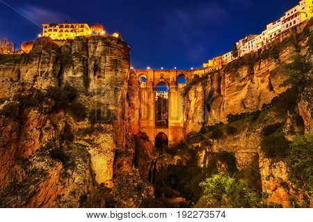 The popular historic landmark of spectacular Puente Nuevo, New Bridge, illuminated at night, over Guadalevin River in town of Ronda, Andalusia, Spain.