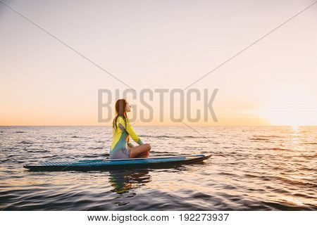 Stand up paddle boarding on a quiet sea with warm sunset colors. Young woman is relaxing on ocean