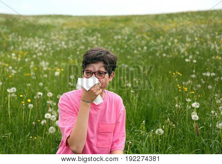 Allergic child blows his nose with white handkerchief in springtime