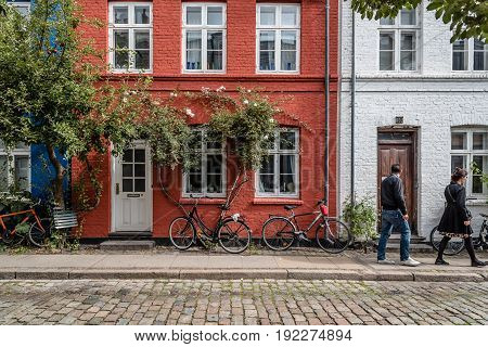 Copenhagen Denmark - August 12 2016. Picturesque old brick colorful houses in historical city centre of Copenhagen a cloudy day of summer with bicycles parked