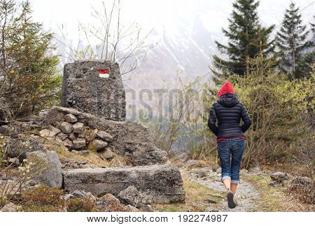 Young Woman With Red Hood Walks On Mountain Path