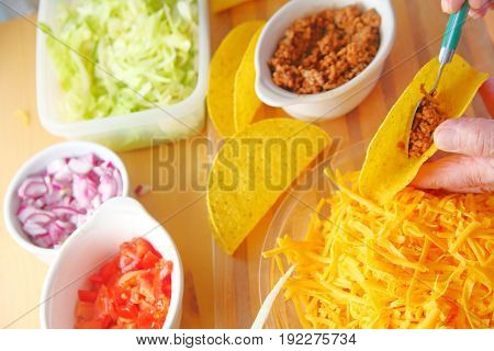 A man puts ground beef into a taco shell with grated cheese shredded lettuce chopped tomatoes and onions nearby