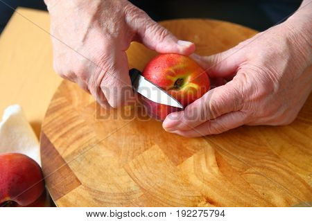 A man uses a paring knife to peel a fresh peach over a wood cutting board