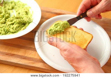 A man spreads mashed avocado on a slice of brioche toast.