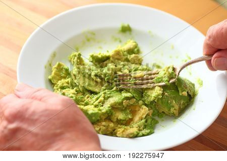 Older man mashes an avocado using a fork point of view