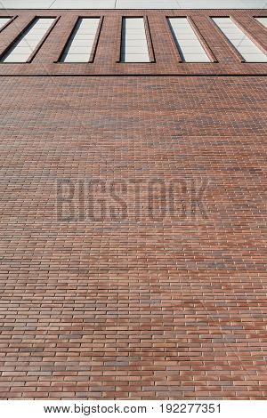 Red brick wall facade background with high windows. Industrial building from 19th century in Berlin, Germany.