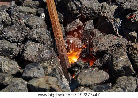 The metal billet is heated in burning coals