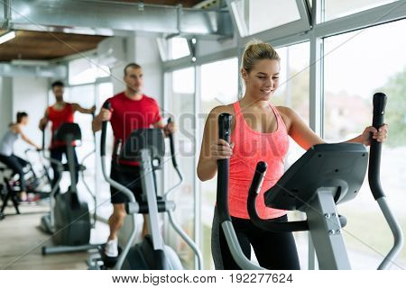 Gropu of people doing on elliptical trainer in gym