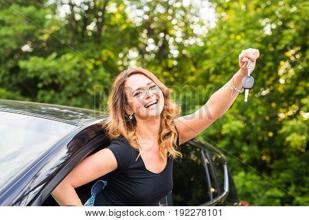 Beautiful young woman driver showing car keys in hand.