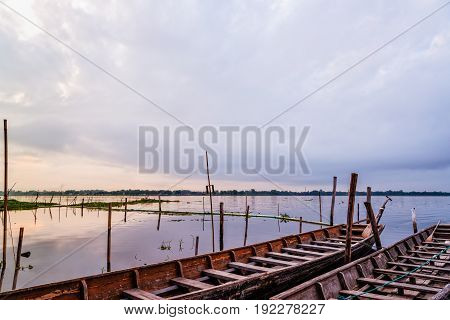 Old wooden boat floating on the water amidst the natural landscape of the morning at Kwan Phayao Lake in Phayao Province Thailand