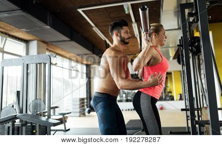 Woman doing squats in gym with her personal trainer
