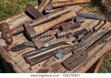 On the table are tools for the blacksmith (hammers forceps chisels coal ladle and others)