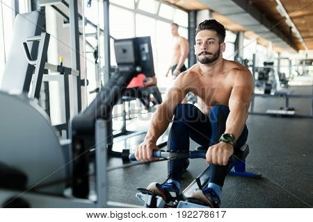 Young handsome man workout with rowing machine in gym