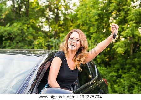 Young cheerful joyful smiling gorgeous woman holding up keys to her first new car. Customer satisfaction.