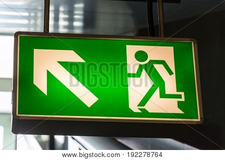 A green lighted emergency exit sign close up