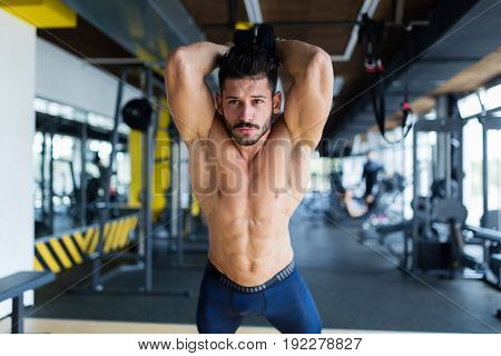 Young attractive man doing trx exercise in gym