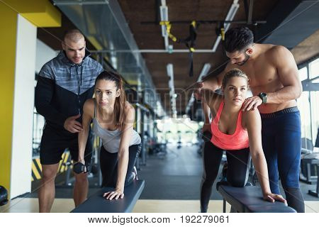 Young women in gym doing exercises with their trainers