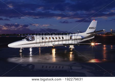 Private Jet on Wet Runway At Sunrise