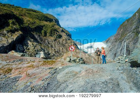 SOUTH ISLAND, NEW ZEALAND- MAY 23, 2017: Unidentified couple enoying the view of the Franz Josef Glacier and valley floor, Westland, South Island, Franz Josef Glacier National Park, in New Zealand.