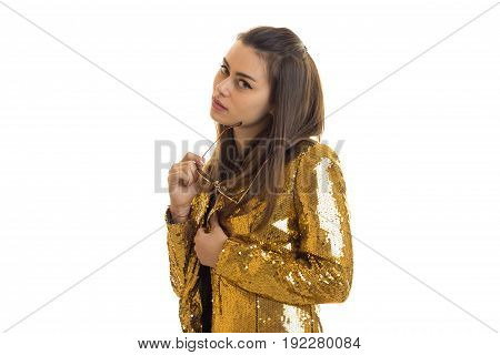 Cutie young brunette girl in golden jacket looks at the camera isolated on white background