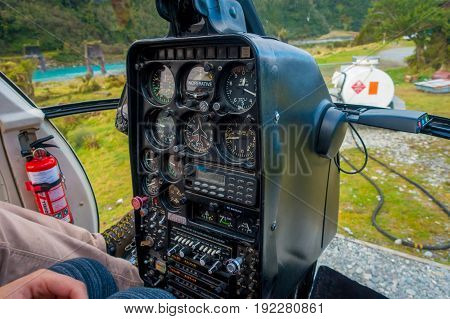 SOUTH ISLAND, NEW ZEALAND - MAY 21, 2017: Pilot using command cabin of the helicopter, in South Westland's Southern Alps, New Zealand.