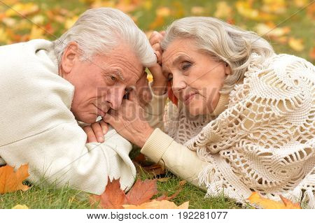 Portrait of senior couple lying on green grass with autumnal leaves
