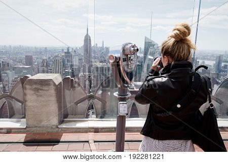 Tourist taking photos of New Yorks skyline on view point
