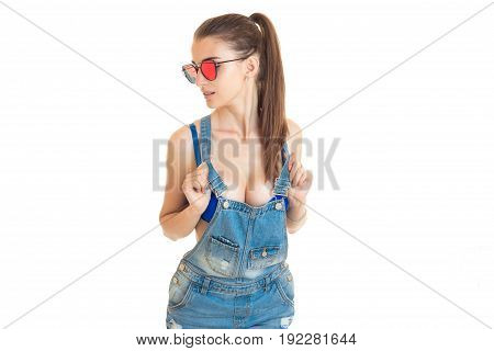 Sexy girl in denim overalls and blue bra with big silicon breasts isolated on white background